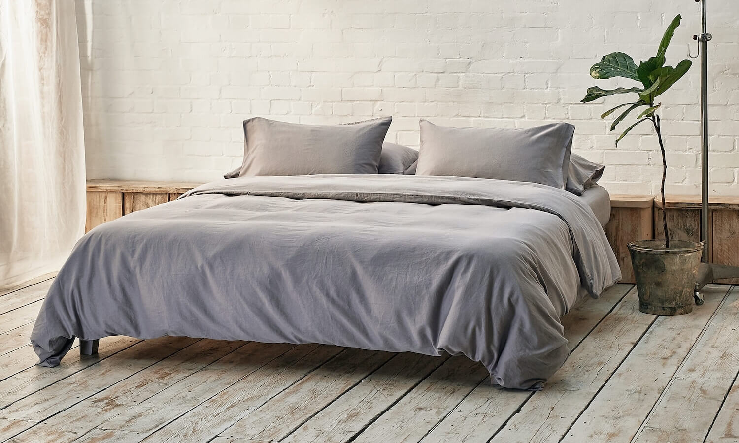 silver grey bedding on bed in a modern room