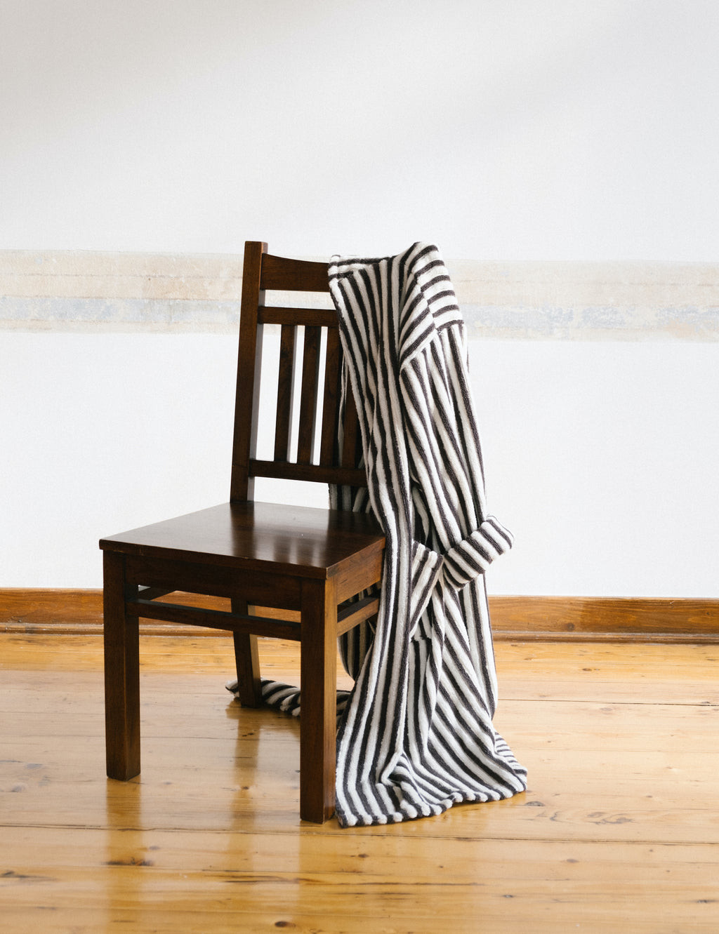 brown and white striped cotton bathrobe hanging on wooden chair