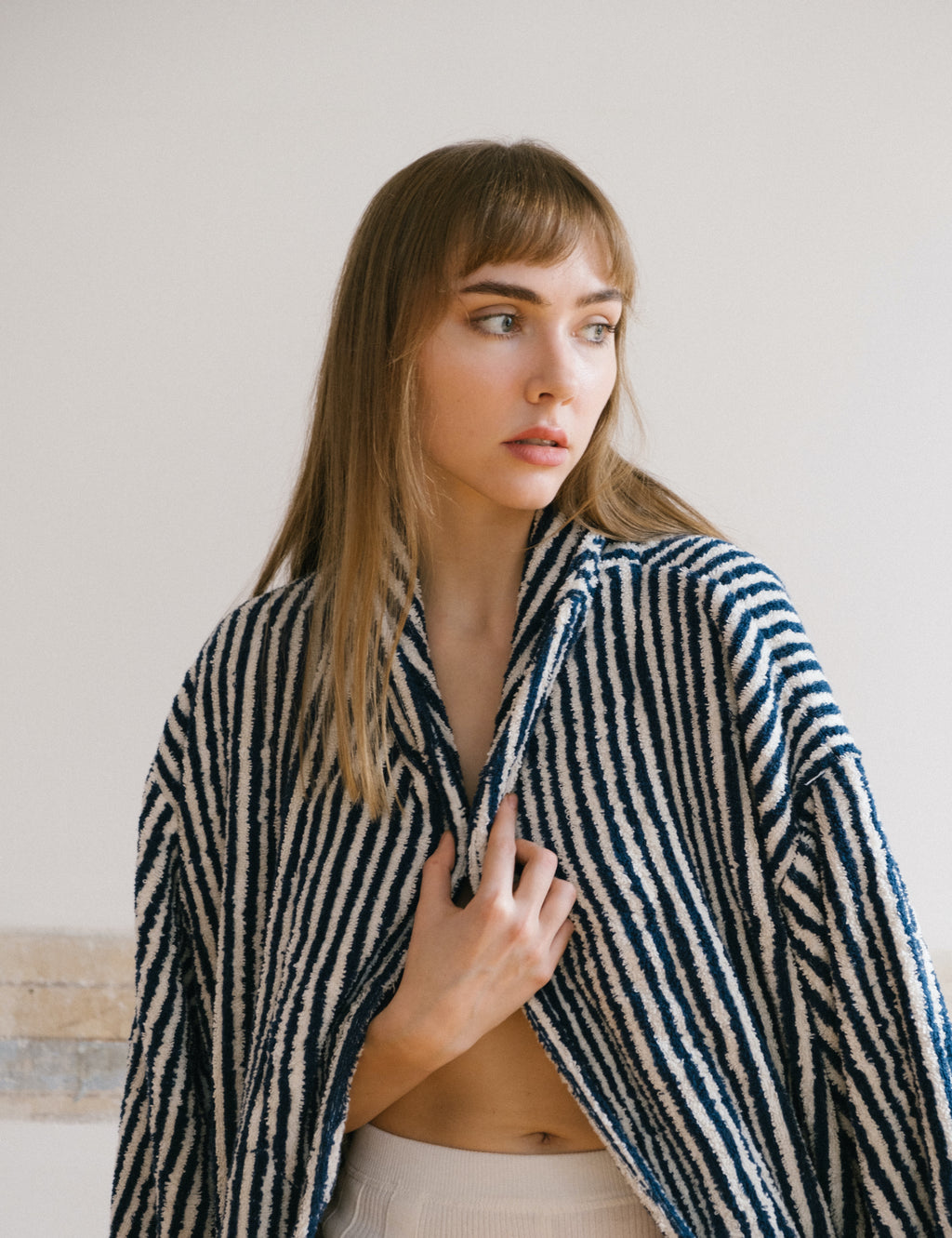 woman carrying white and navy striped cotton bathrobe over her shoulders