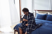 man wrapped in navy checkered bedspread