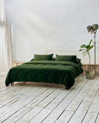 Modern bedroom with dark green bedding and exposed brick wall