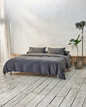 dark grey duvet cover set in front of white brick wall