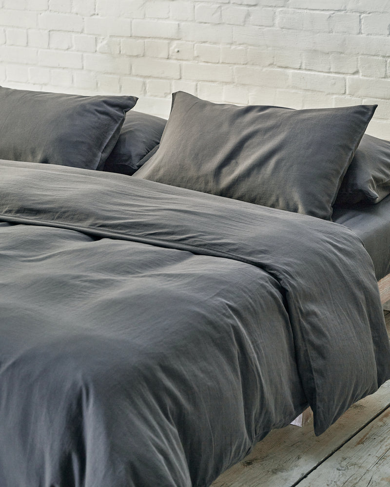 dark grey duvet cover set in a modern bedroom with exposed brick