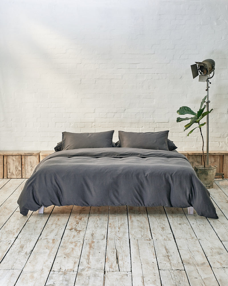 Modern bedroom with dark grey bedding and exposed brick wall
