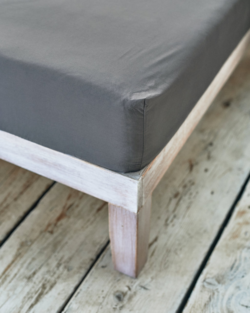 tight fitted corner of dark grey cotton bedsheet