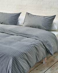 navy and white striped bedding set in an industrial bedroom