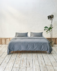 Modern bedroom with navy and white striped bedding and exposed brick wall