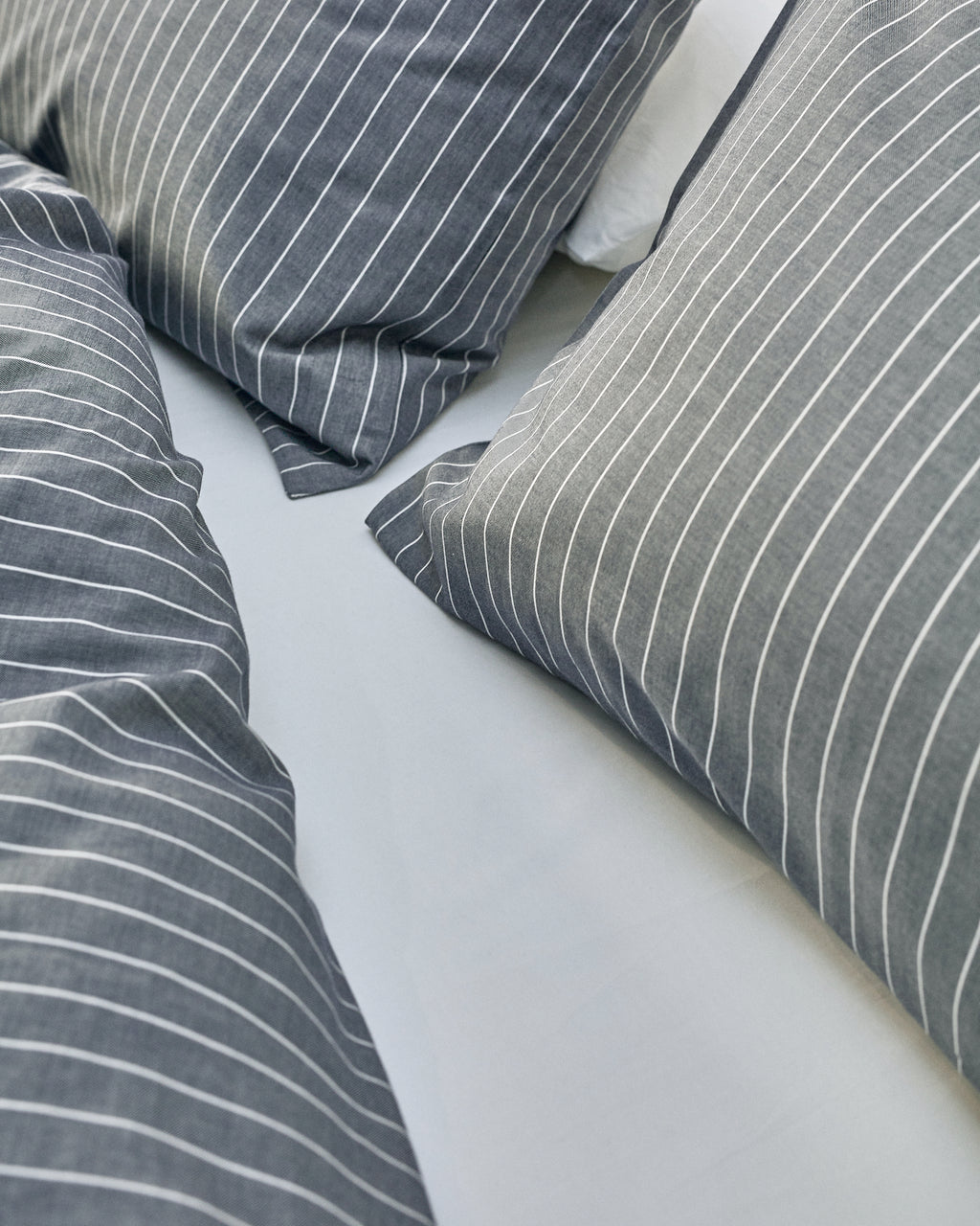 navy and white striped duvet cover set in front of white brick wall