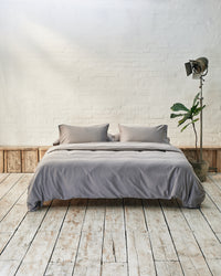 Modern bedroom with silver grey bedding and exposed brick wall
