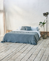 Modern bedroom with light blue bedding set with bedspread and scatter cushions in