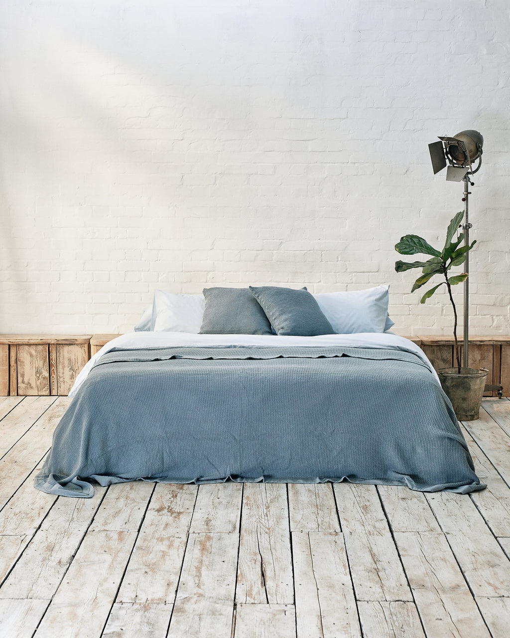 light blue bedding set with blue waffle bedspread and scatter cushions in an industrial bedroom