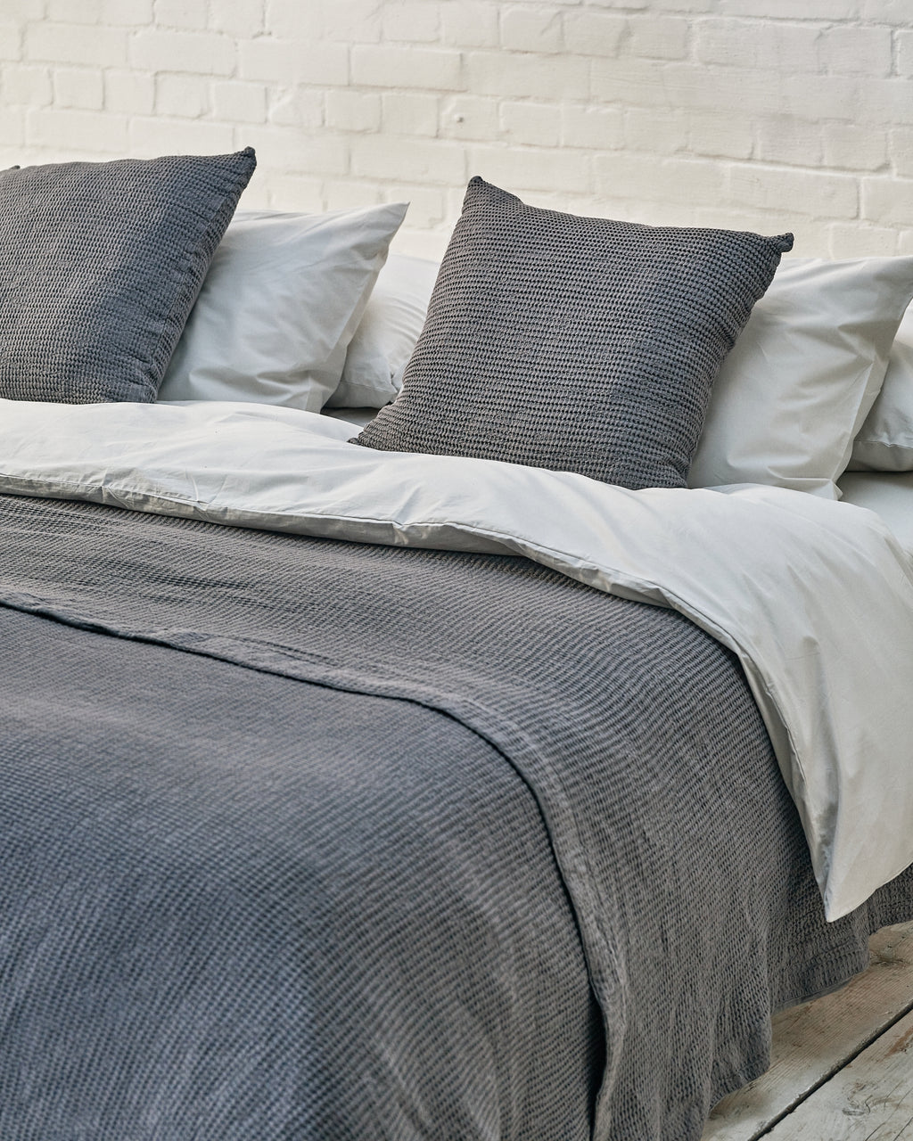 light grey luxury bedding set with dark grey waffle bedspread and scatter cushions