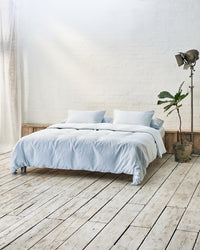 light blue duvet cover set in front of white brick wall