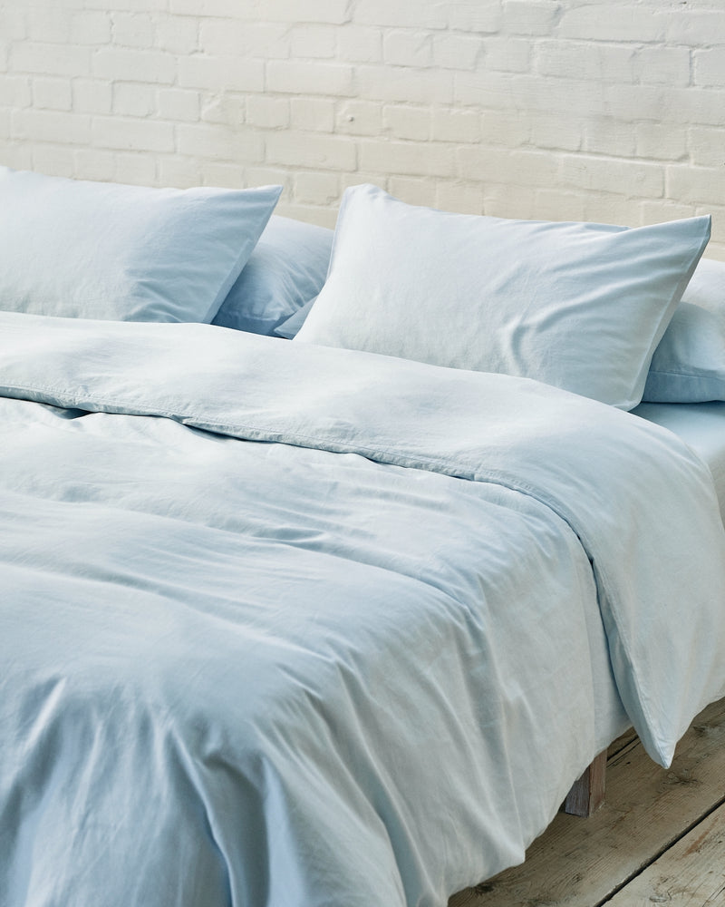 light blue duvet cover set in a modern bedroom with exposed brick