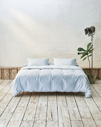 Modern bedroom with light blue bedding and exposed brick wall