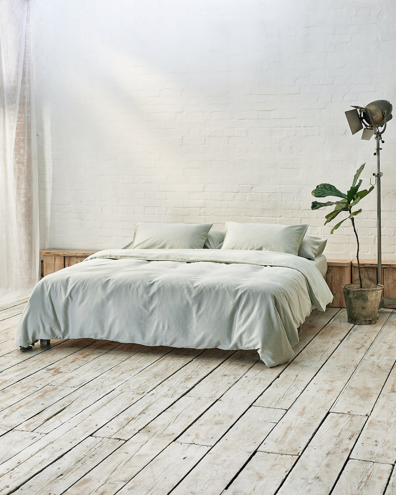 light green duvet cover set in front of white brick wall