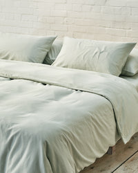 light green bedding set in an industrial bedroom