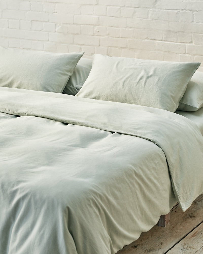 light green duvet cover set in a modern bedroom with exposed brick