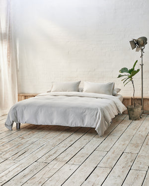 light grey duvet cover set on a platform bed