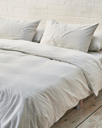 light grey duvet cover set in front of white brick wall