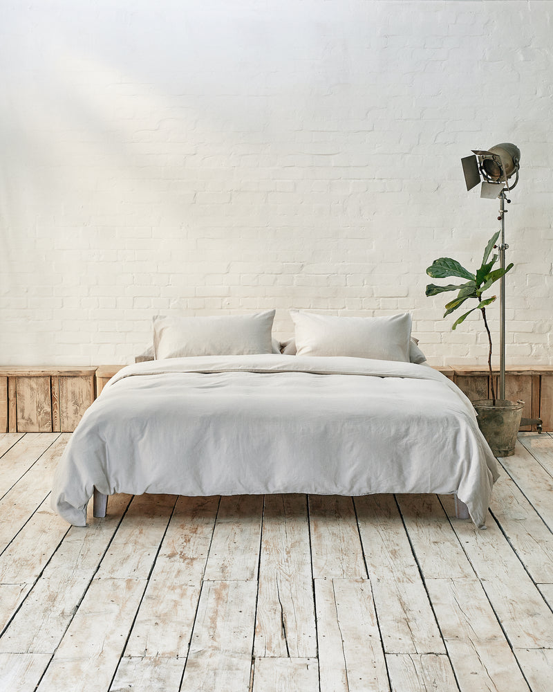 Modern bedroom with light grey bedding and exposed brick wall