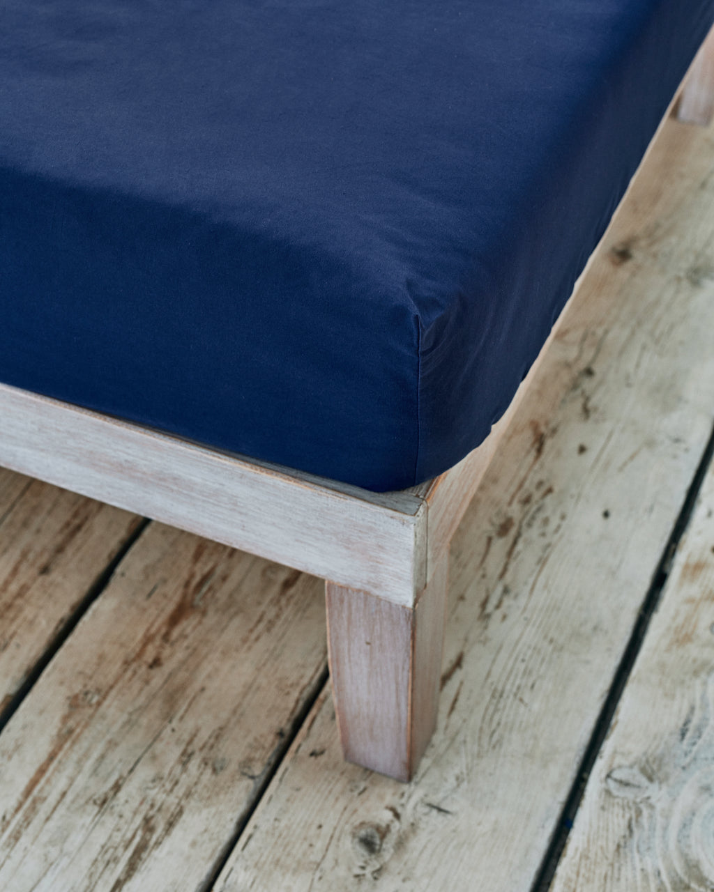 tight fitted corner of navy blue cotton bedsheet