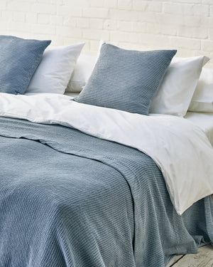 white luxury bedding set with blue waffle bedspread and scatter cushions
