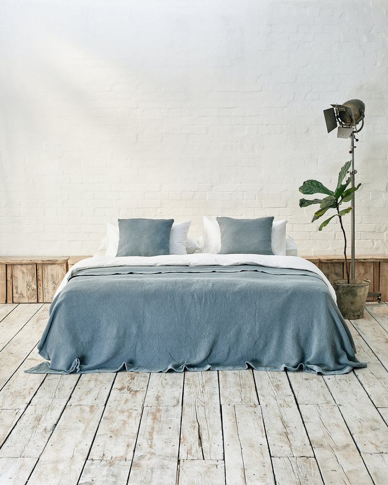 white bedding set with blue waffle bedspread and scatter cushions in an industrial bedroom