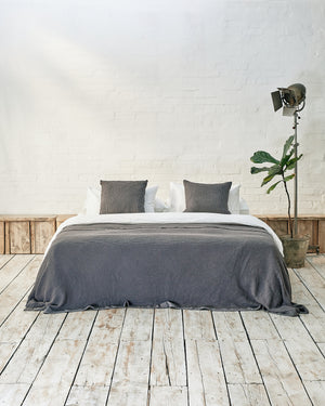 white bedding set with dark grey waffle bedspread and scatter cushions in an industrial bedroom