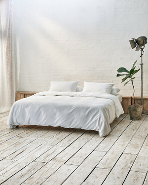 Modern bedroom with white bedding and exposed brick wall