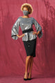 short haired black woman posing against burgundy cloth background wearing a caxlz foxy silver sequin tunic top styled with a black obi belt pencil skirt heels and a matching caxlz silver sequin faace mask