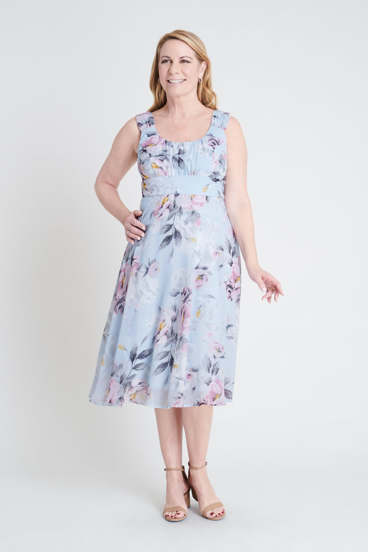 Woman posing wearing Aqua Carly Aqua Floral Print Midi Dress from Connected Apparel