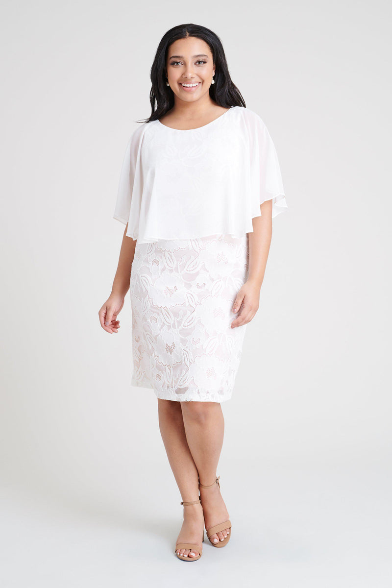 Woman posing wearing Ivory Elsa Ivory Lace Cape Dress from Connected Apparel