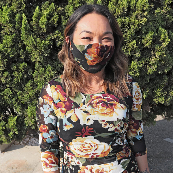 Woman posing wearing Mustard Mustard Floral Mesh Face Mask from Connected Apparel