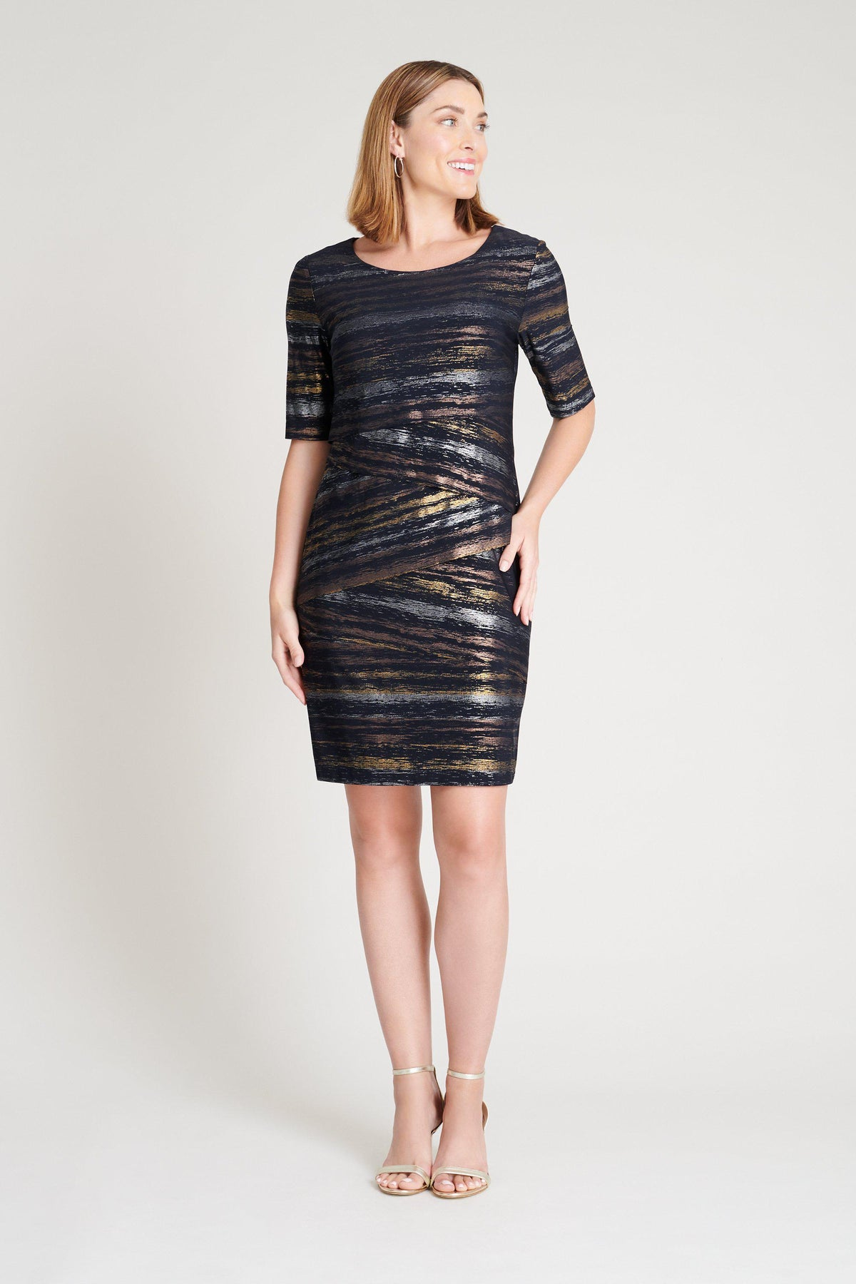 woman-wearing-connected-apparel-Brandy Asymmetrical Navy & Metallic Striped Dress-posing-on-plain-background