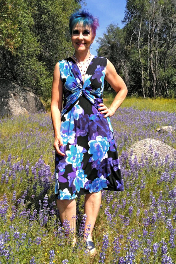 Woman posing wearing Black Reese Blue Floral Print Dress from Connected Apparel