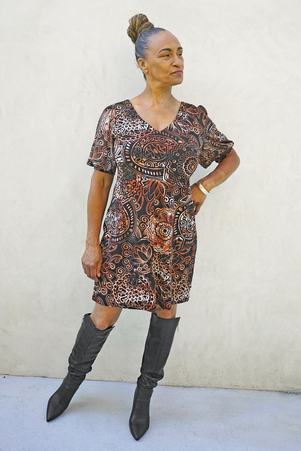 Woman posing wearing Rust Sadie Rust Statement Sleeve Dress from Connected Apparel