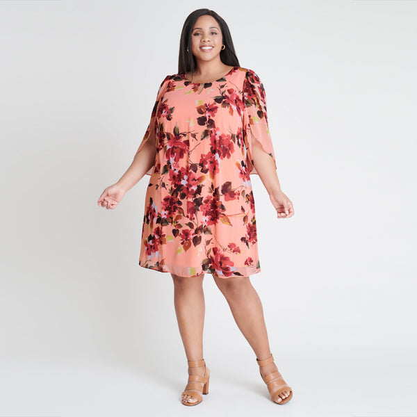 Woman posing wearing Salmon Stevie Salmon Floral Print Dress from Connected Apparel