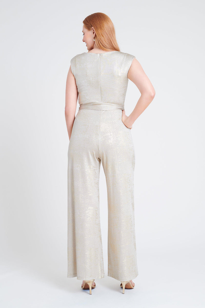 Woman posing wearing Gold Uptown Gold Foil Print Jumpsuit from Connected Apparel