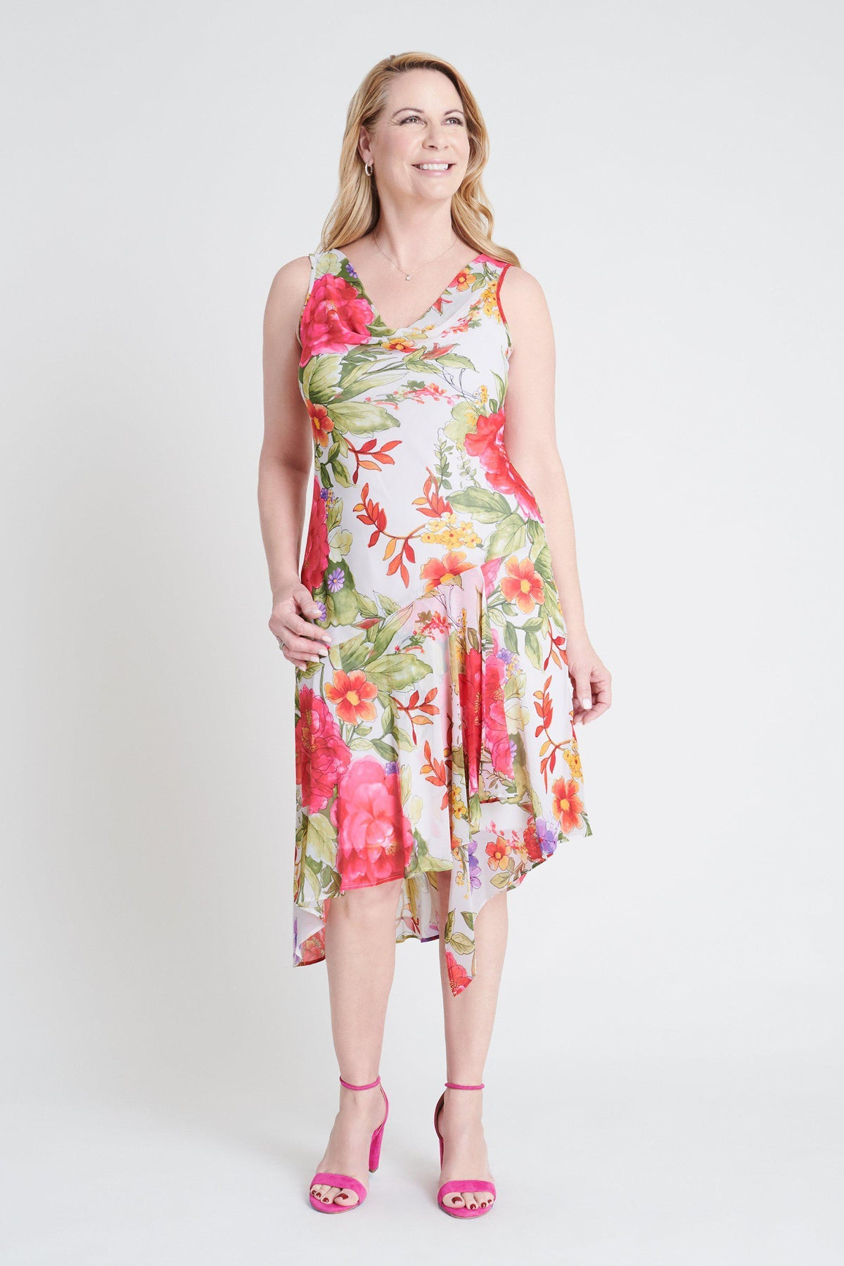 Woman posing wearing Champagne/Pink Willa Pink Floral Print Asymmetrical Dress from Connected Apparel