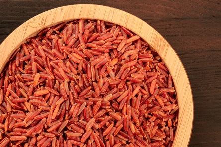 frederic fekkai red rice grains from France Camargue Rice Water in wooden bowl on brown table