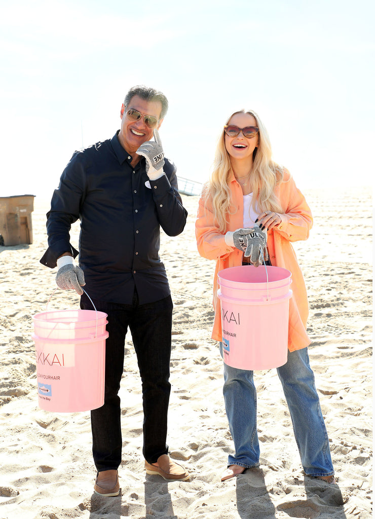 Founder Frederic Fekkai & star Dove Cameron posing on Santa Monica Beach with pink trash-collecting buckets in the middle of a beach clean-up with environmental advocacy organization Heal The Bay