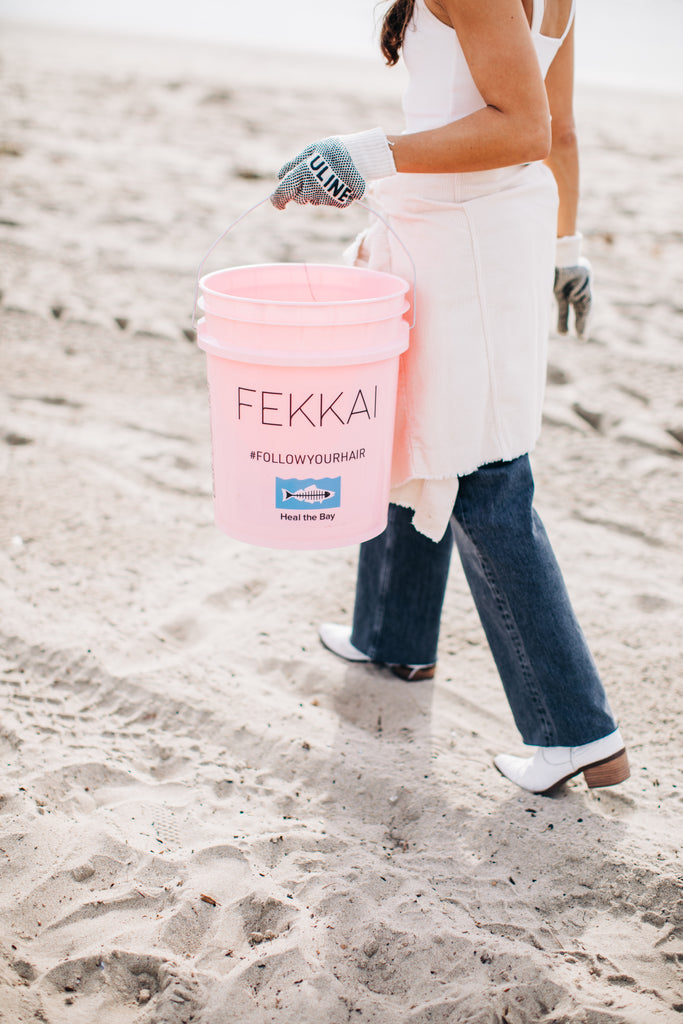 A FEKKAI x Heal The Bay beach clean-up volunteer with her pink trash-collection bucket on Santa Monica Beach