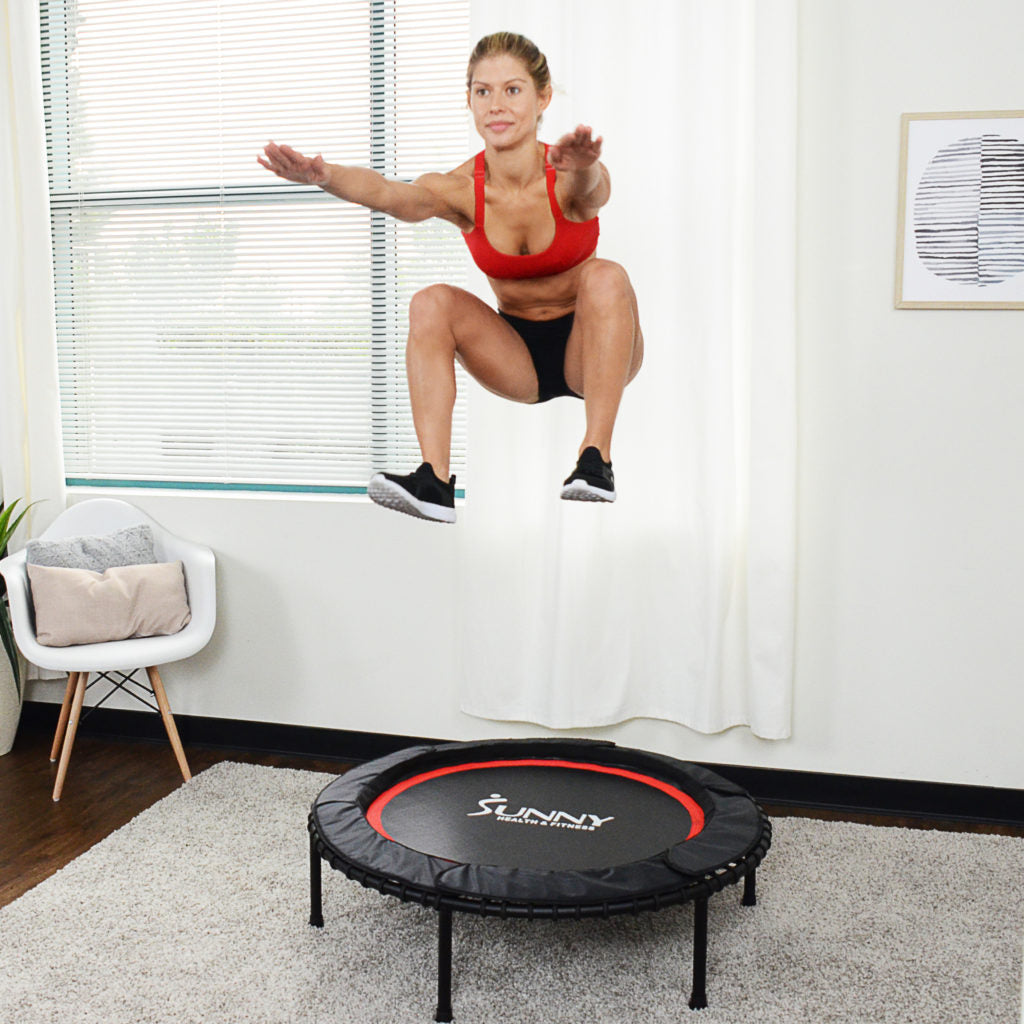 woman in mid-air in squatting form with trampoline below