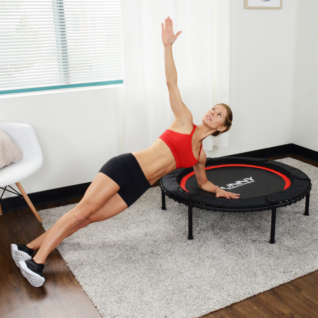 woman doing side planks while leaning on trampoline