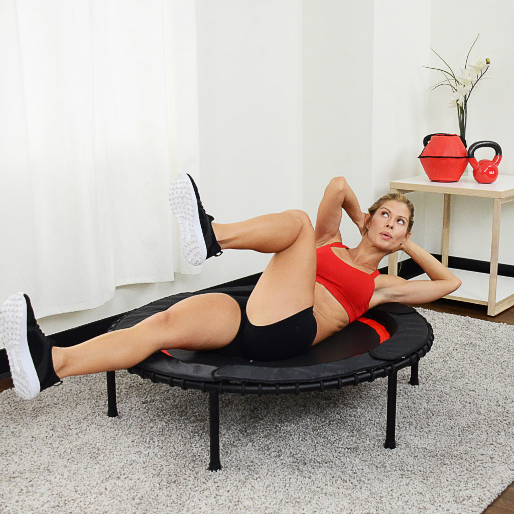woman doing bicycle crunches on trampoline