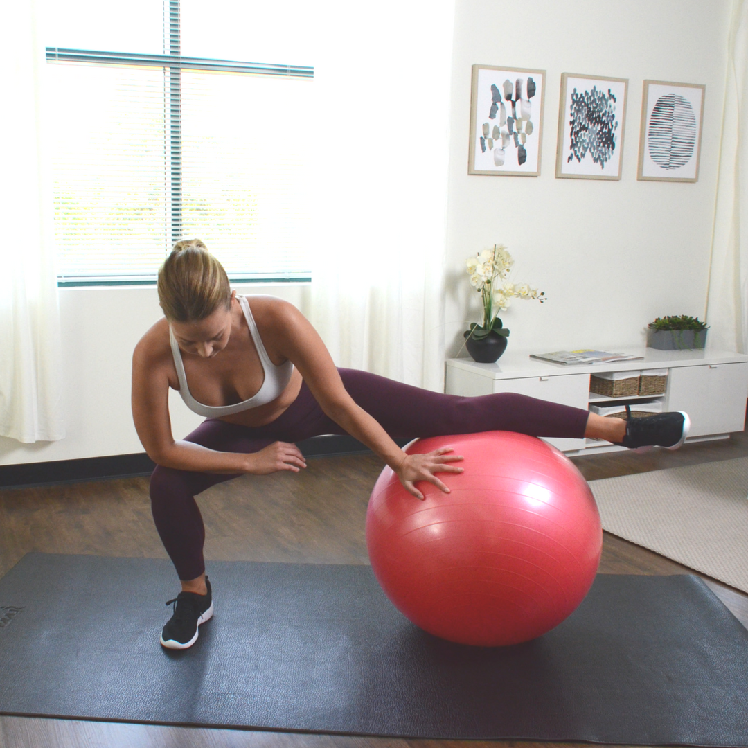 woman leaning over with one leg stretching on gym ball