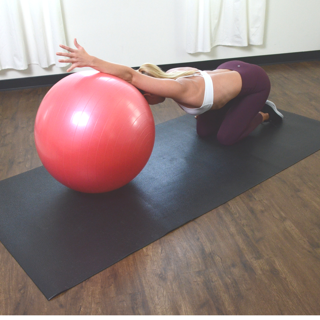 woman kneeling forward with arms on gym ball stretching