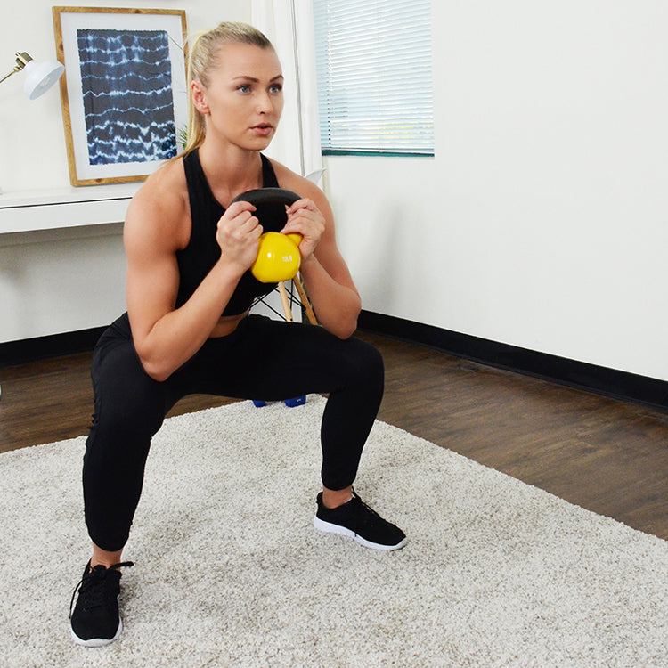 woman holding yellow kettlebell with both hands while holding squats