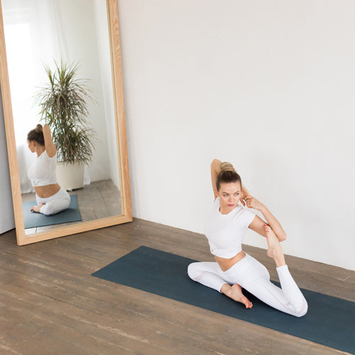a lady is stretching in front of a mirror